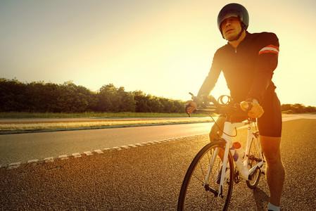 Sun rises behind man ready to ride bike