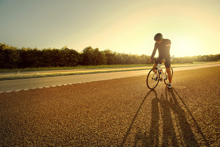 Bicyclist pausing with long shadow from sun