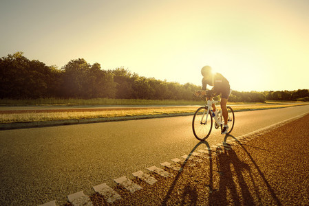 Fit person riding a bike in sunset