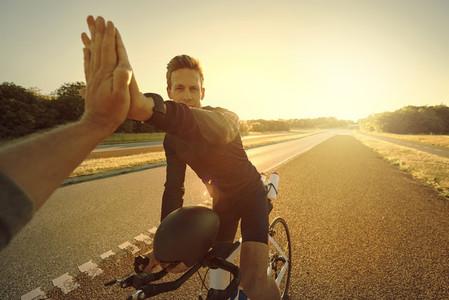 Man on bike giving a high five