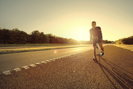 Sportsman on bicycle parked on a highway