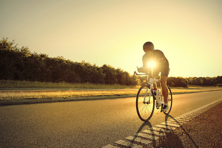 The athlete on bicycle on a road