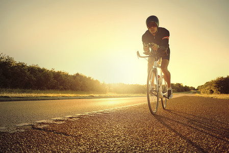 The sportive man exercising on bike on highway