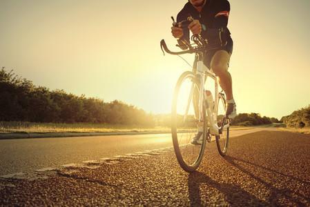 Athlete on bike riding on empty road