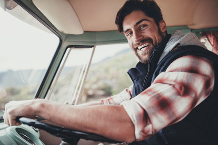 Handsome man driving van on his road trip
