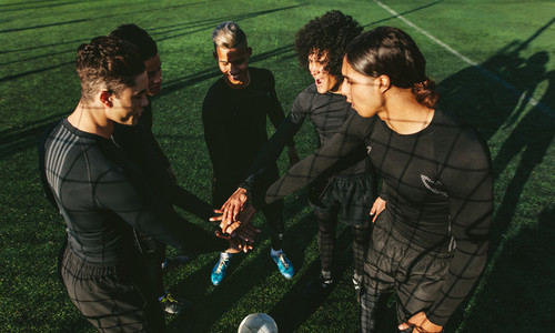 Soccer team stacking hands at football field