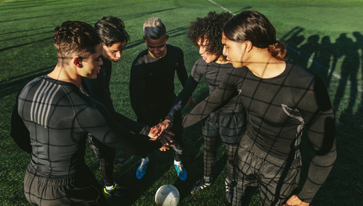Five a side football team putting their hands together