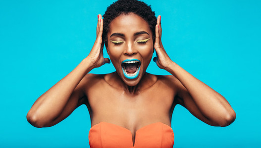 African woman with colorful makeup screaming