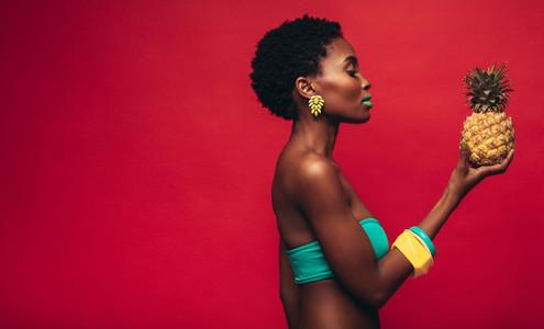 Black woman looking at pineapple