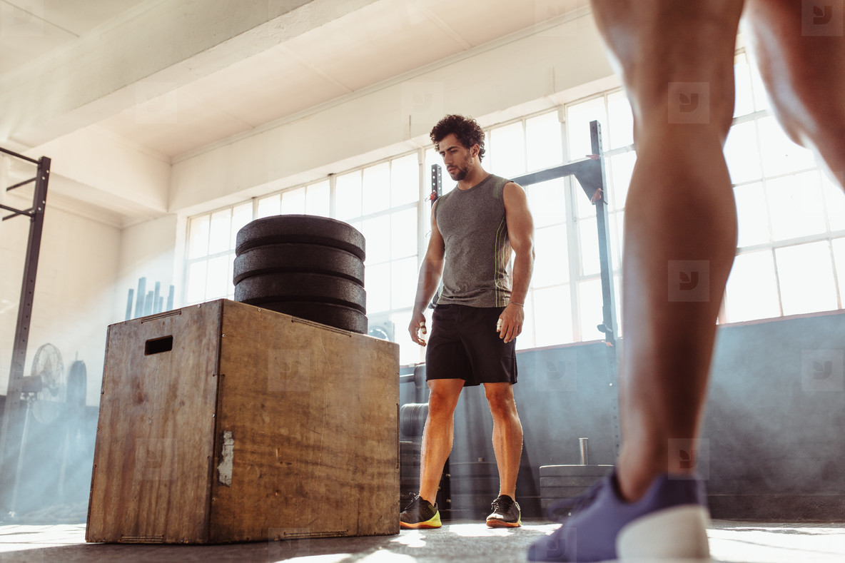 Determined fit man doing box jumping in health club