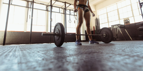 Woman exercising with barbell in health club