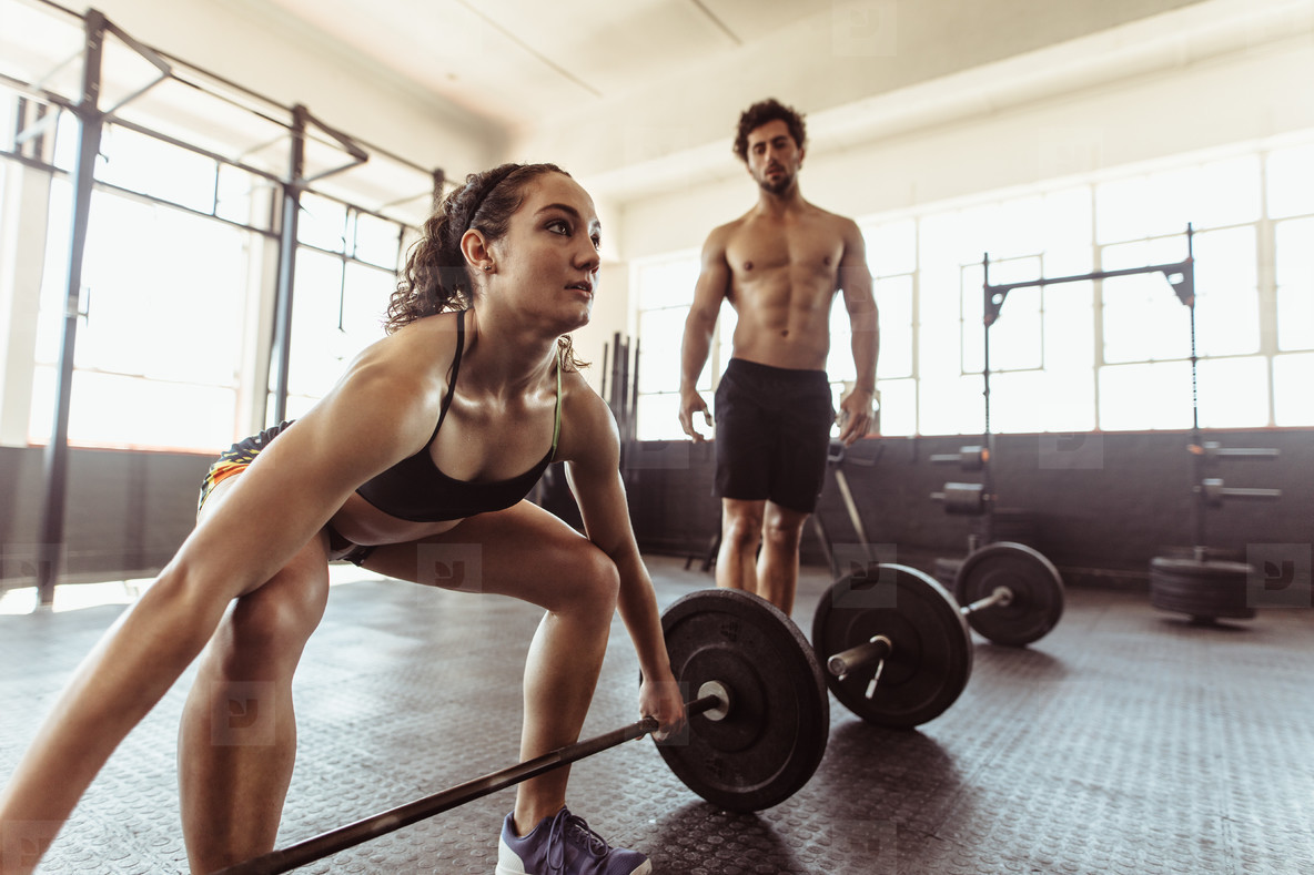 Female athlete lifting weights at cross training gym
