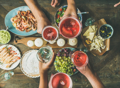Flat lay of friends hands eating and drinking together