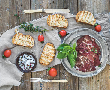 Smoked meat in vintage silver plate with fresh basil  cherry tomatoes and bread slices over rustic wood