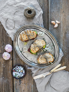 Rustic sandwich set  Sandwiches with smoked meat  cucumber  onion  herbs and spices on a metal dish over rough wood