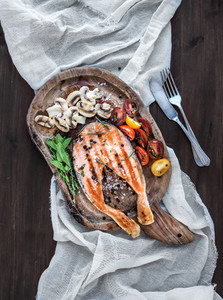 Grilled salmon steak with fresh herbs  roasted mushrooms  cherry