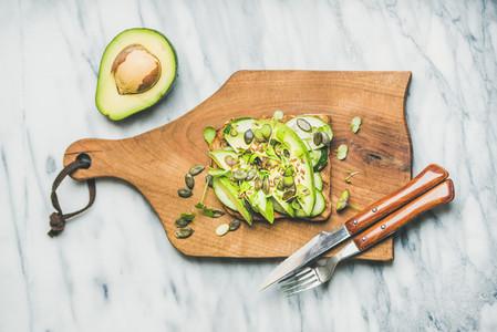 Healthy green veggie breakfast concept with sandwich on board