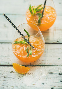 Refreshing cold alcoholic summer cocktail with orange in glasses