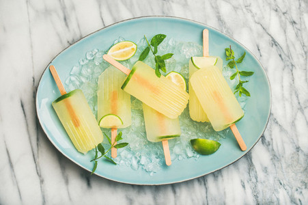 Summer lemonade popsicles with lime  mint leaves and chipped ice