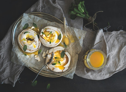 Merengues with lemon curd  fresh mint on silver tray  beige kitchen towel