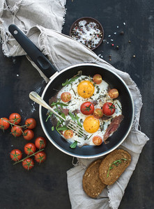 Pan of fried eggs  bacon and cherry tomatoes
