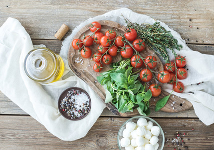 Basil  cherry tomatoes  mozarella  olive oil  salt  spices on rustic chopping board