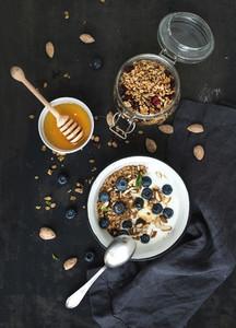 Healthy breakfast  Oat granola with fresh blueberries  almond  yogurt and mint