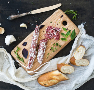 Meat gourmet snack  Salami  garlic  baguette and herbs on rustic wooden board