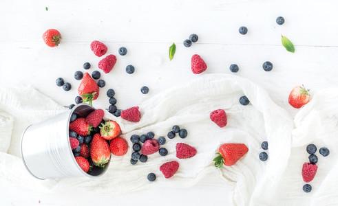 Metal bucket  strawberries  raspberries  blueberries and mint leaves  white wooden background