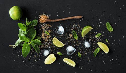 Ingredients for mojito  Fresh mint  limes  ice  sugar over black backdrop