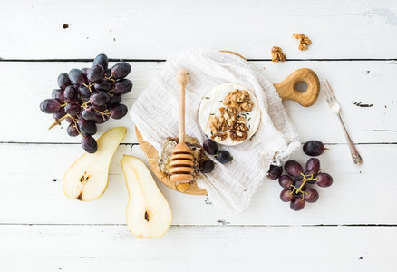 Camembert cheese with grape  walnuts  pear and honey on vintage metal plate