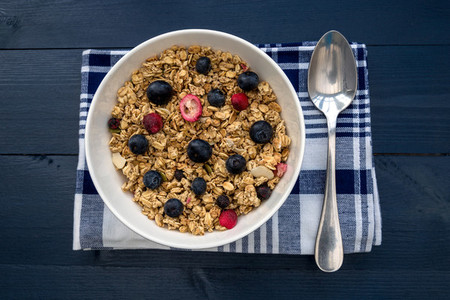 Breakfast granola cereal bowl with fruit and berries and spoon