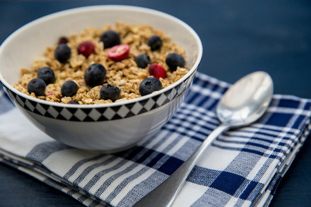 Bowl of breakfast cereal on blue table with silver spoon