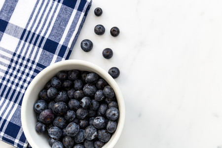 Bowl of blueberries fruit on white marble background