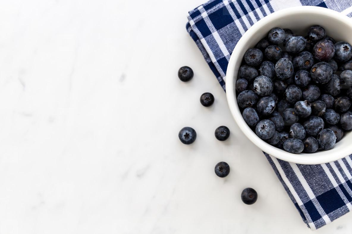 Bowl of fresh blueberries on white marble background