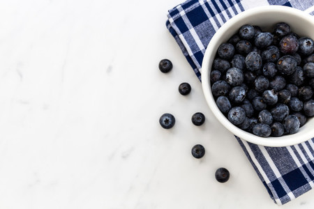 Bowl of fresh blueberries on white marble background