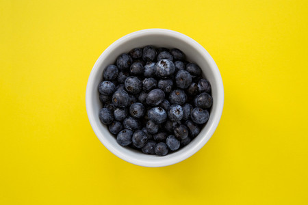 Bowl of blueberries on yellow background