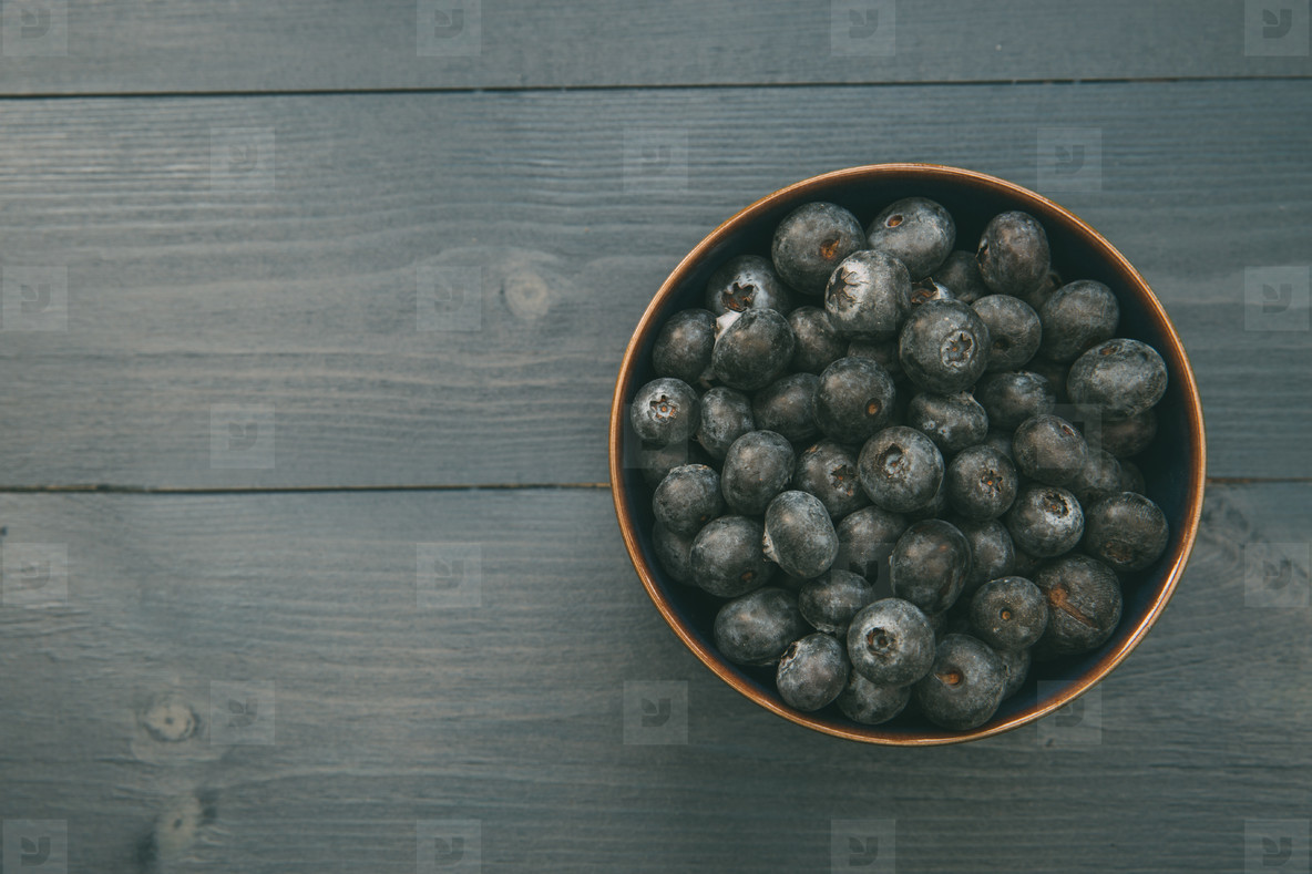 Bowl of blueberries on wood table with copy space