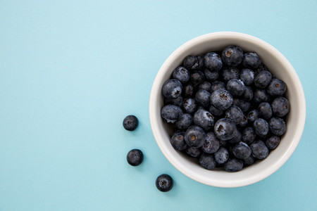 Bowl of blueberries on blue background with copy space