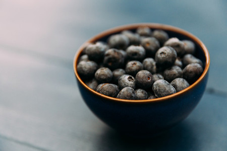 Bowl of blueberries on wood table
