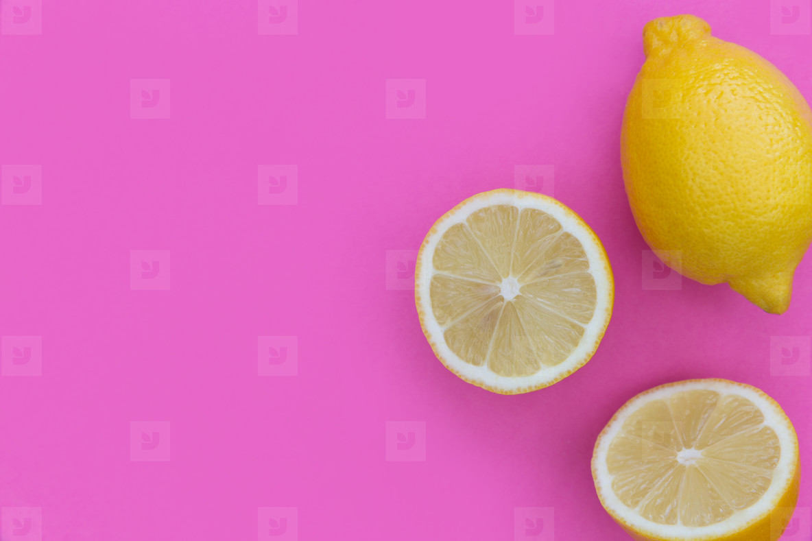 Sliced lemons on bright pink background with copy space