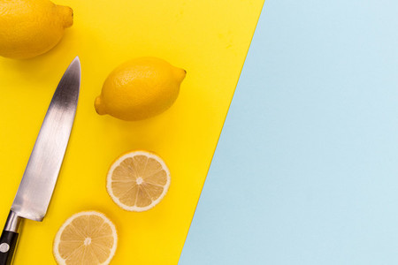 Sliced lemons and knife on bright yellow and blue background