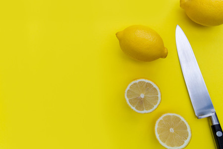 Sliced lemon fruits and knife on bright yellow background with c