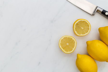 Sliced lemon fruits and knife on white marble background with co
