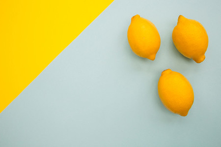 Bunch of fresh lemons on blue and yellow background