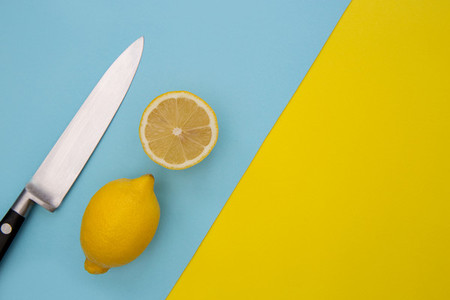 Sliced lemons and knife on minimal yellow and blue background