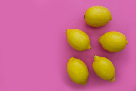 Bunch of lemons on bright pink background