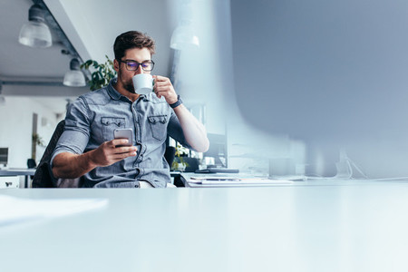 Male designer with mobile phone drinking coffee