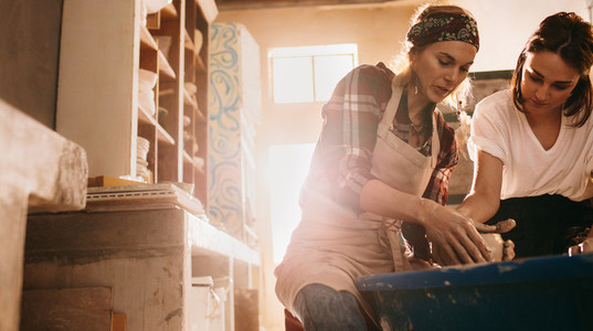 Woman teaching the art of pot making