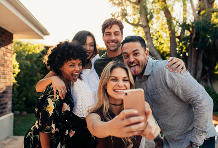 Young friends at housewarming party taking selfie